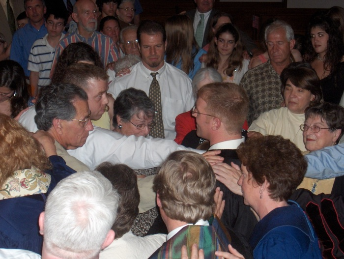 A photo of a crowd of people surrounding a man being ordained, laying hands on his shoulders